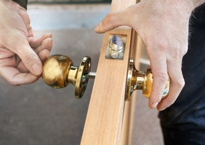 Install interior door, joiner mount knob with lock, hand close-up.